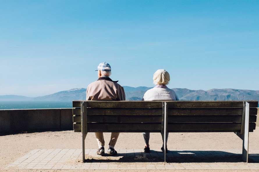 An elderly couple sat on a bench looking at a blue sky and moutains in the distance